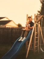 Dad and me sliding on our swing set in 1994